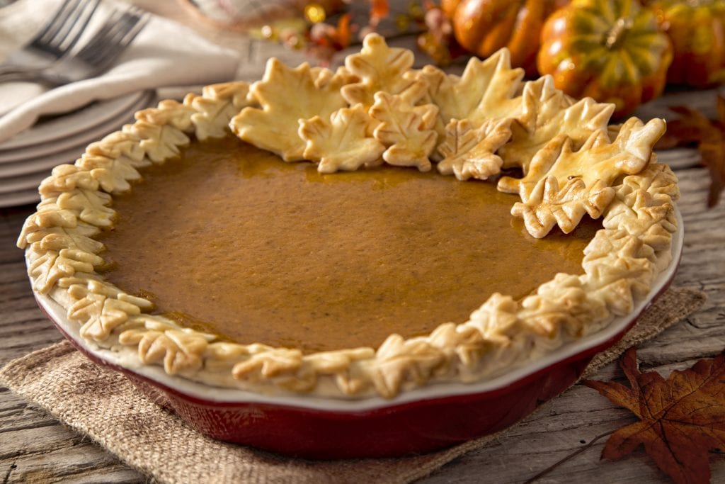 pumpkin pie. The pumpkin pie is decorated with a ornate crust. The pie crust is made of oak and maple leaf cut outs. The pie sits in a fall scene decorated with fall or autumn pumpkins and gourds. The pumpkin pie sits on a rustic farm table with warm light spilling on the scene
